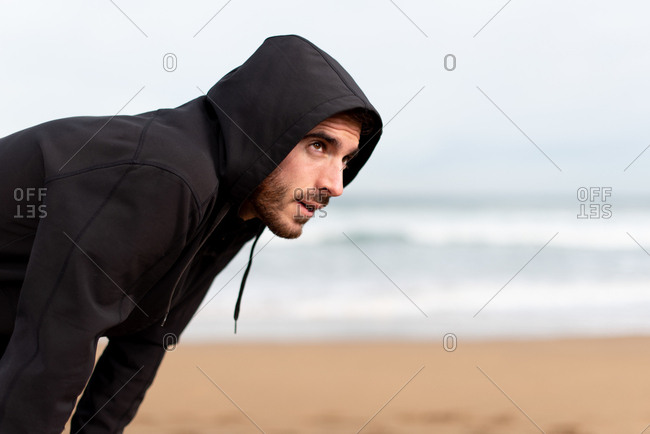 Bearded male gymnast in black hoodie standing with hands on knees and looking away with sandy seashore on blurred background