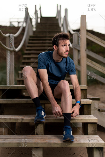 Bearded male gymnast in sports clothing sitting on wooden stairs while preparing to workout and looking away
