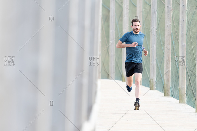 Highly motivated bearded male athlete in blue t shirt and shorts running outdoors under cover looking at camera