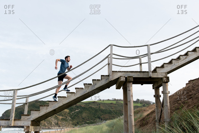 Side view from below of male athlete in sports clothing running upstairs with green mountains and sky on background
