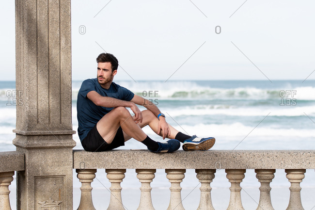 Side view of bearded male gymnast in active wear resting on rocked fence after train and looking away with sea and sky on blurred background