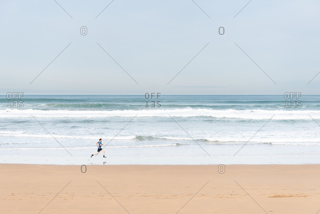 Side view of male athlete in active wear running during empty sandy beach