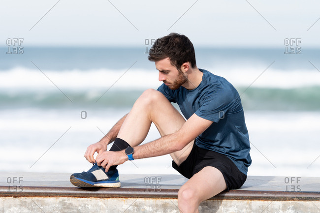 Black haired bearded male athlete in blue t shirt and shorts sitting on fence and tying shoelaces with blue sea and sky on blurred background