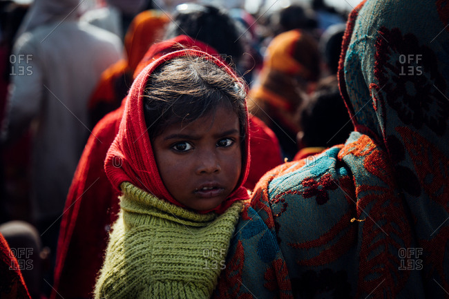 Allahabad city, India - FEBRUARY, 2018: Little girl in red headscarf and green knitted sweater sitting in arms of crop woman walking on street in crowd of pilgrims during Praying Kumbh Mela Festival