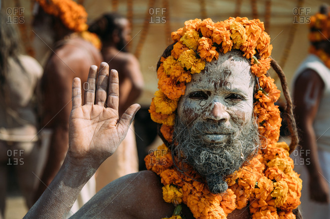 Allahabad city, India - FEBRUARY, 2018: Hindu sadhu with face painted with ash and saffron flowers around head and neck standing on street and waving hand at camera during Praying Kumbh Mela Festival