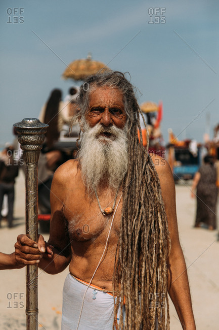 Allahabad city, India - FEBRUARY, 2018: Aged bearded Hindu man with dreadlocks and naked torso standing on street with big metal stick in hand and looking at camera during Praying Kumbh Mela Festival