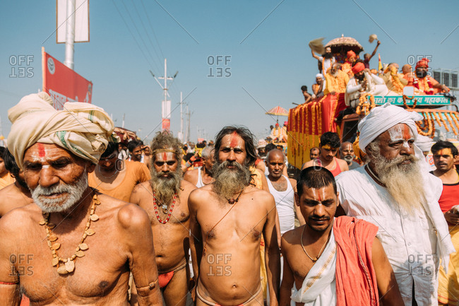 Allahabad, India - February, 2018: Mature old men in turbans and bright loincloth with naked torso walking on street in Praying Kumbh Mela Festival