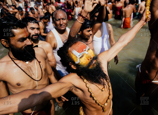 Allahabad, India - February, 2018: Inspired bearded man with wooden beads on naked body and colored face raising hands in crowd making ritual in water during Praying Kumbh Mela Festival