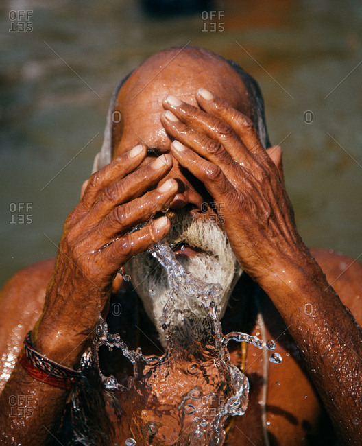 Allahabad, India - February, 2018: Gray-haired man splashing and performing ritual bath in water in Praying Kumbh Mela Festival