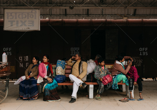 Praying Kumbh Mela Festival, Allahabad, India - February, 2018: Women in red and blue clothes festive man and kids waiting for transport sitting on station bench and looking away