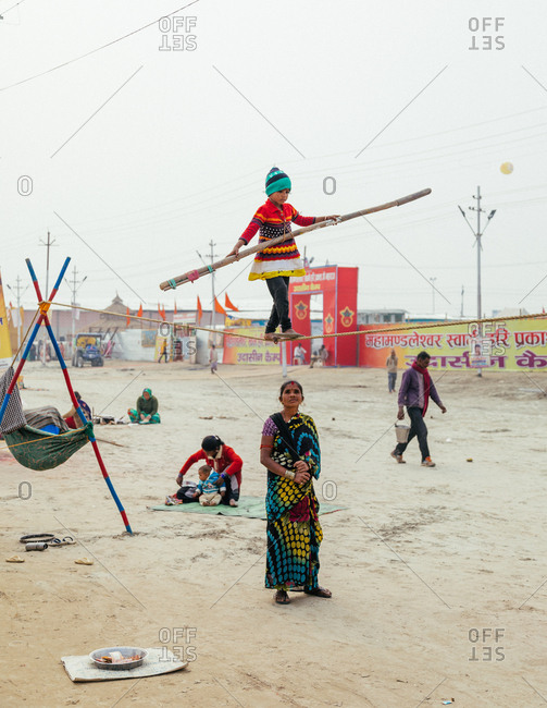Allahabad, India - February, 2018: Festivities in square where child tightrope walker walking along rope while girl in sari looking up