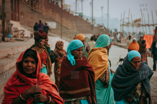 Allahabad, India - FEBRUARY, 2018: Group of aged poor Indian women wearing typical colorful clothes with scarfs on heads walking on river bank next to port in village