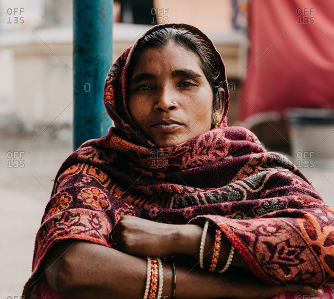 Allahabad city, India - FEBRUARY, 2018: Close-up portrait of hindu woman wearing traditional costume sitting on street during Praying Kumbh Mela Festival