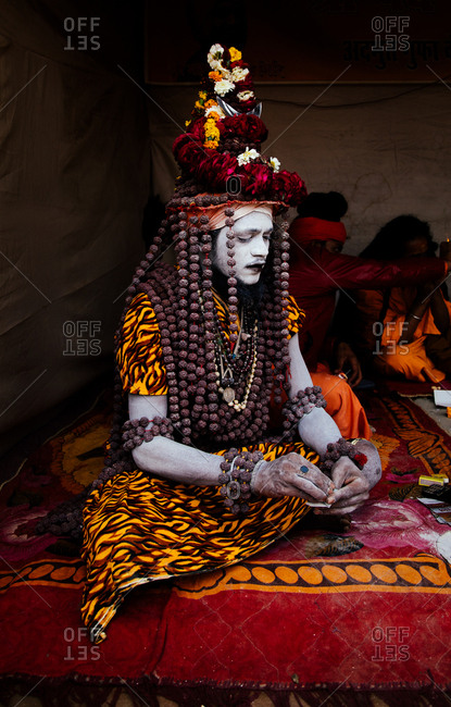 Allahabad city, India - FEBRUARY, 2018: Hindu sadhu holy man with painted face wearing traditional colorful costume sitting on carpet during Praying Kumbh Mela Festival