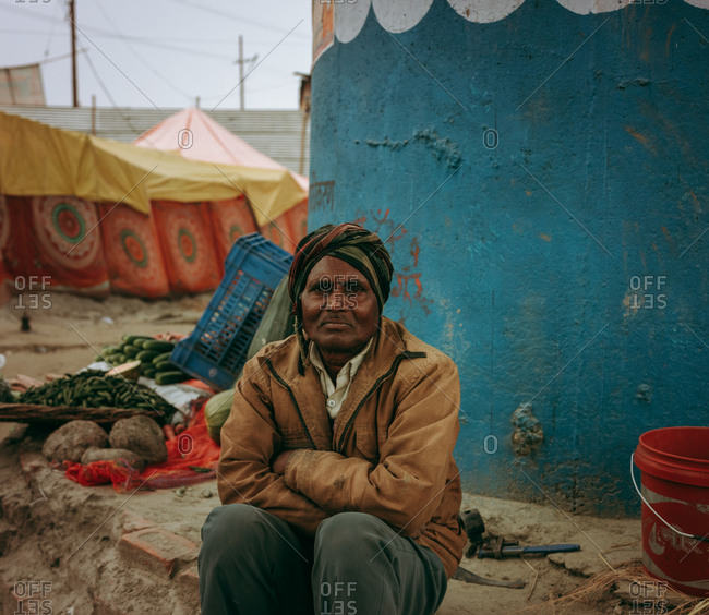 Allahabad, India - February, 2018: Old man sitting in sandy place along round tents during Praying Kumbh Mela Festival