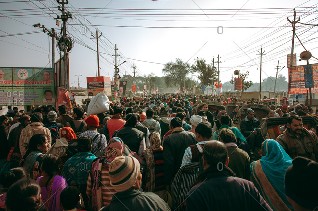 Allahabad, India - February, 2018: From behind view of festive people moving in street in honor of Praying Kumbh Mela Festival