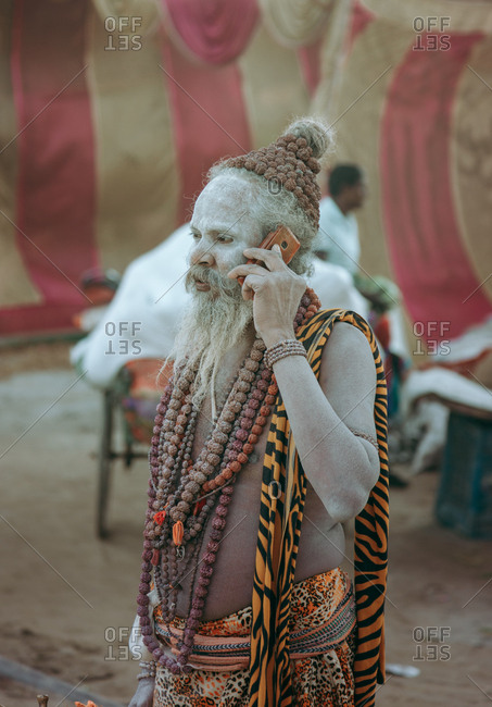 Allahabad city, India - FEBRUARY, 2018: Hindu sadhu with face painted with standing on street talking on the phone during Praying Kumbh Mela Festival