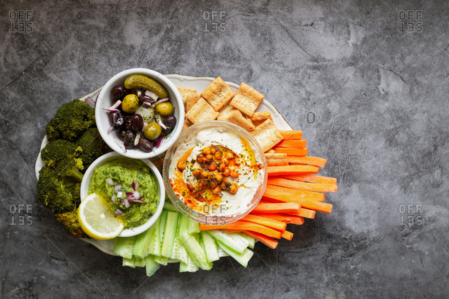 From above appetizing healthy hummus green sauce cut carrot cucumbers and green broccoli salted cucumbers decorated with sliced lemon in white bowls on table