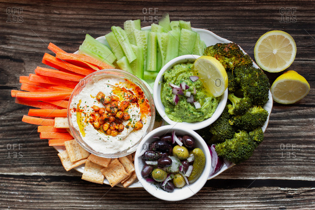 From above appetizing healthy hummus, green sauce, cut carrots, cucumbers, broccoli, and salted cucumbers decorated with sliced lemon in white bowls on wooden table