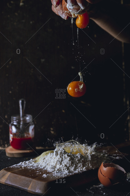 Crop person breaking eggs over flour while preparing dough on table with eggshell and glass pot and egg falling on black background