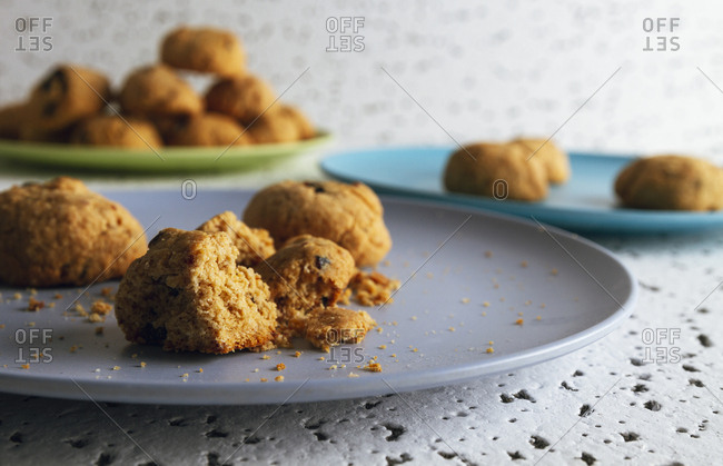 Fresh brown bitten cookies with chocolate crumbs lying on colorful ceramic plates on white spotted table against blurred white wall