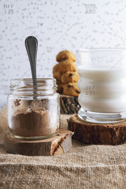 Transparent jar of cacao powder and glass of dairy beverage in composition with blurred tasty brown cookies on wooden coasters standing on sackcloth against spotted white wall