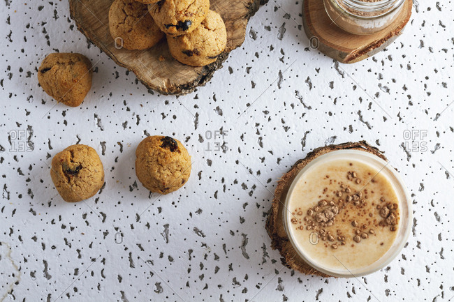 Tasty brown cookies on wooden coasters standing on sackcloth and transparent jar of cacao powder and glass of dairy beverage