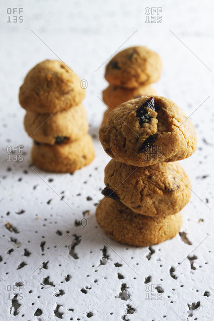 Fresh homemade brown cookies with chocolate on white table against blurred white wall
