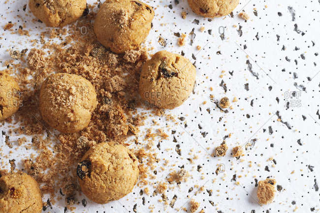 High angle of fresh brown cookies with chocolate crumbs spilling in mess on white table against blurred white wall