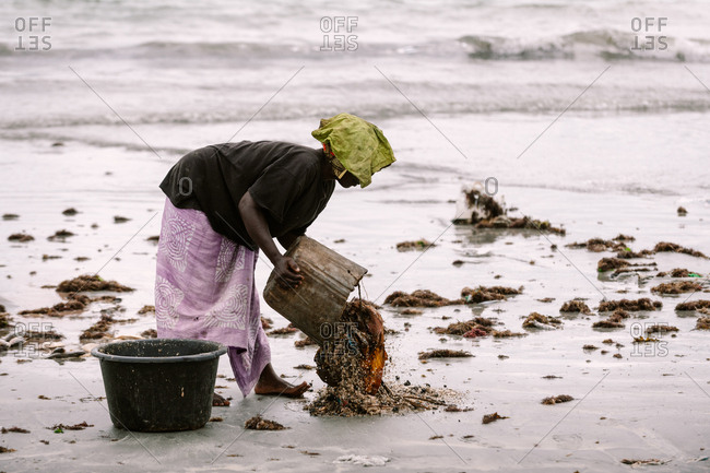 Gambia, Africa - August 6, 2019: Side view of black female pouring dirty water with clothing from bucket on ground during washing on shore