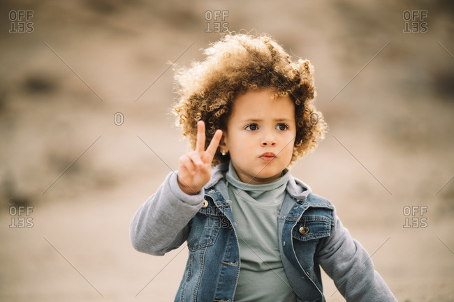 Adorable curly ethnic child dressed in casual clothes on beige blurred background and thoughtfully looking away