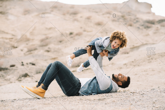 Cheerful bearded ethnic man dressed in stylish clothes lying down holding curly happy ethnic toddler on bright sandy hills at daytime