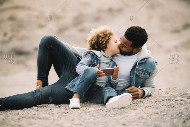 African American bearded casual man lying on sandy ground leaning on elbow and bending leg at knee looking at curly ethnic toddler in denim clothes sitting beside with mobile phone