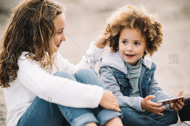 Smiling casual curly haired child resting on ground with crossed legs holding mobile phone while content girl sitting clasping knees and touching hair of friend with interest