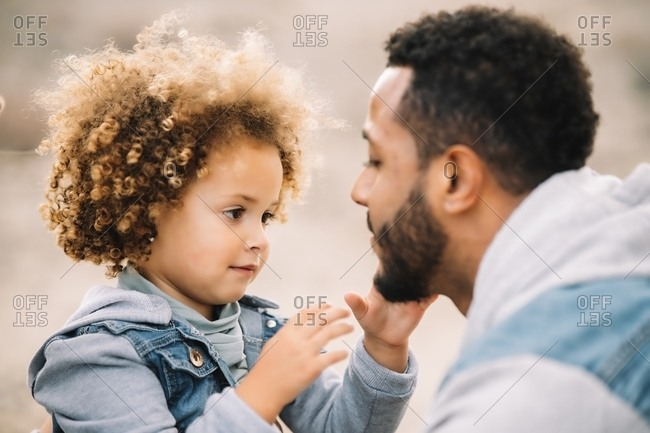 Cheerful bearded ethnic man dressed in stylish clothes playing with curly happy ethnic toddler on bright sandy hills at daytime