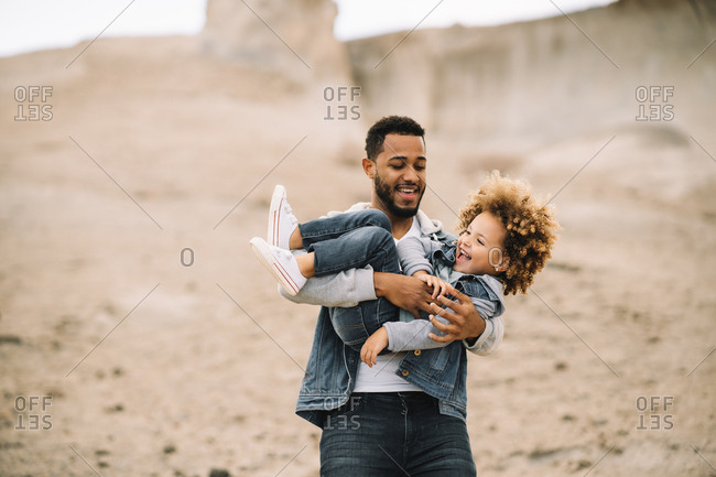 Cheerful bearded ethnic man dressed in stylish clothes holding playing with curly happy ethnic toddler on bright sandy hills at daytime