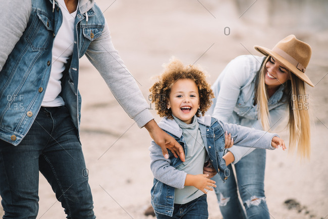 Cheerful multiracial parents in stylish casual clothes holding smiling adorable curly ethnic toddler and having fun at sandy landscape