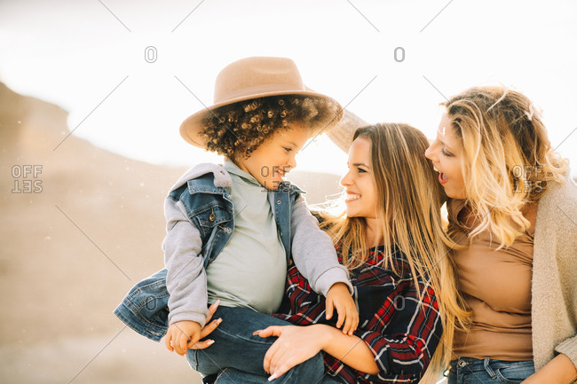Cheerful woman in check shirt holding in arms casual toddler with curly hair while joyful female friend putting hat on child on nature at daytime