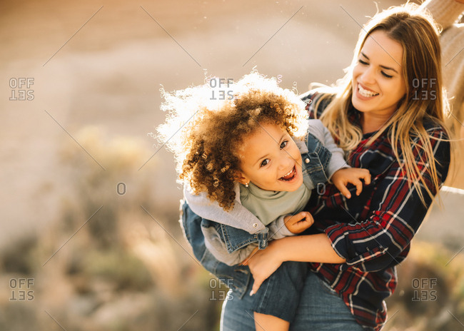 Joyful blonde female in check shirt holding in arms cuddling happy child with curly hair looking at camera outdoors at daytime