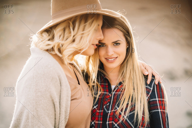 Woman in hat wearing casual clothes tenderly hugging female with long straight hair dressed in check shirt smiling and looking at camera on nature