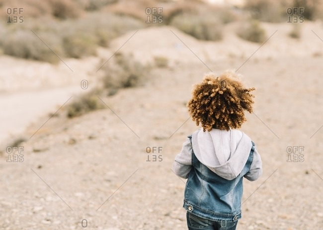 Back view of anonymous curly ethnic child dressed in casual clothes on beige blurred background