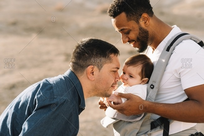 Side view of black casual with male boyfriend holding little calm baby in grey carrier while standing on nature at daytime