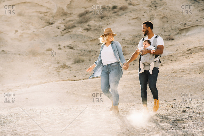Happy black bearded man carrying little baby and holding hand of blonde wife wearing denim shirt jeans and hat while dancing on sandy land