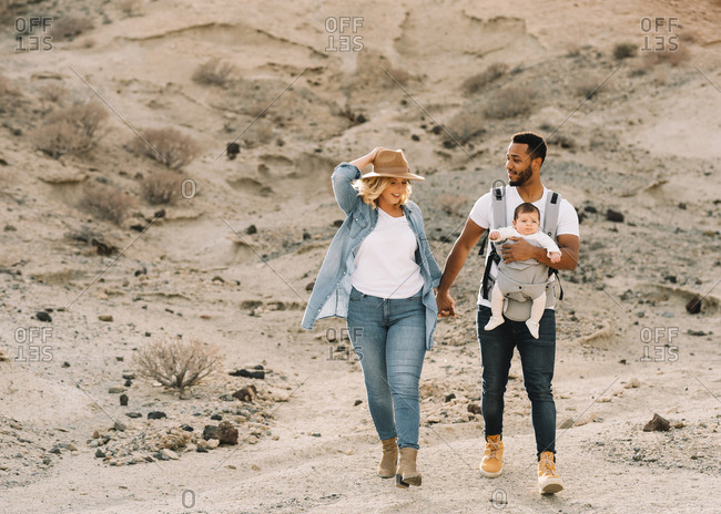Happy black bearded man carrying little baby and holding hand of blonde wife wearing denim shirt jeans and hat while walking on sandy land