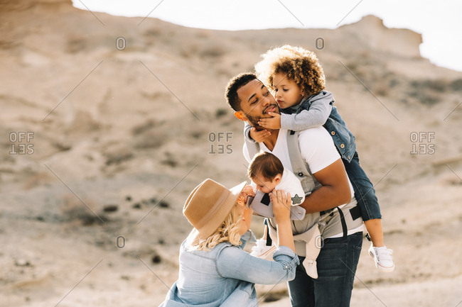 Blonde casual woman in hat laughing while black bearded smiling husband carrying children on nature at daytime