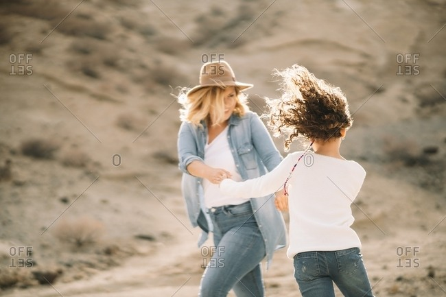 Cheerful blonde woman in denim clothes and hat spinning with smiling casual daughter holding hands while walking in desert landscape