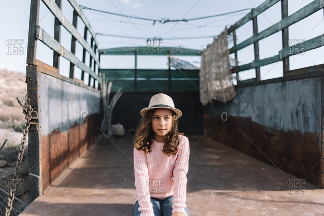 Concentrated girl in straw hat wearing rose knitted jumper sitting in rusty body of old truck putting hands on knees and looking away