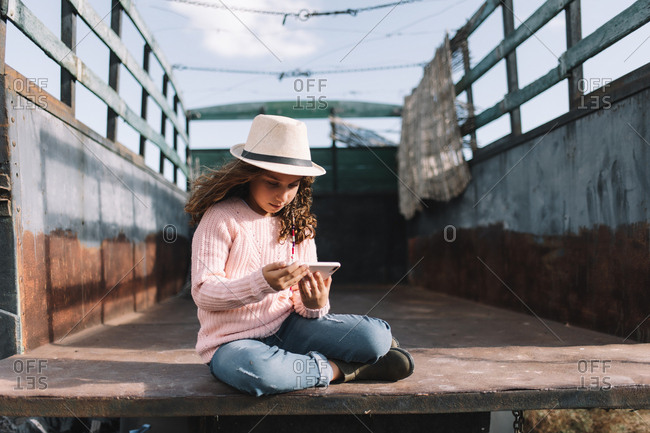Concentrated girl in straw hat rose knitted jumper and jeans sitting in truck body and browsing mobile phone at windy weather