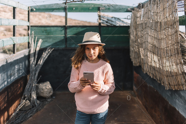 Concentrated girl looking at camera in straw hat rose knitted jumper and jeans standing in truck body and browsing mobile phone at windy weather