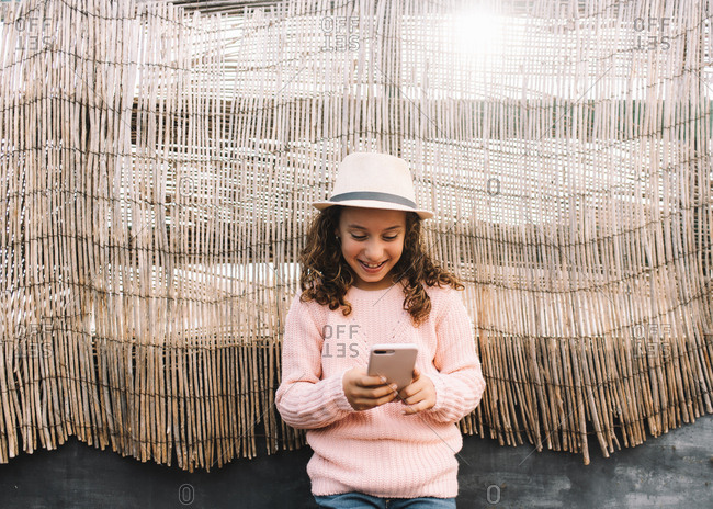 Concentrated girl in straw hat rose knitted jumper and jeans standing on wood background and browsing mobile phone